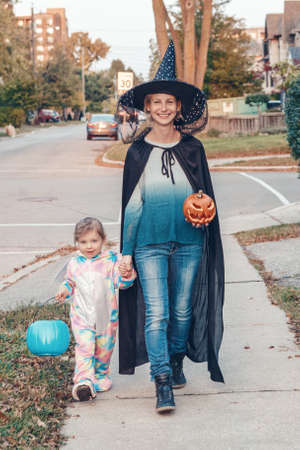 Trick or treat. Mother with baby toddler girl going to trick or treat on Halloween holiday. Mom with kid child in party costumes with basket going to neighbourhood houses for candies, treats.