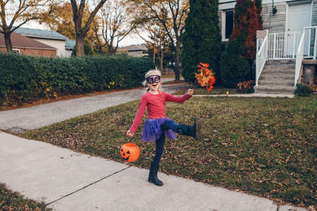 Trick or treat. Happy child girl with red pumpkin basket going to trick or treat on Halloween holiday. Cute child kid in party witch costume going to neighbour houses for candies and treats. Imagens