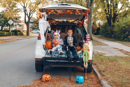 Trick o trunk. Siblings brother and sister celebrating Halloween in trunk of car. Children kids boy and baby girl celebrating October holiday outdoor. Social distance and safe alternative celebration Imagens