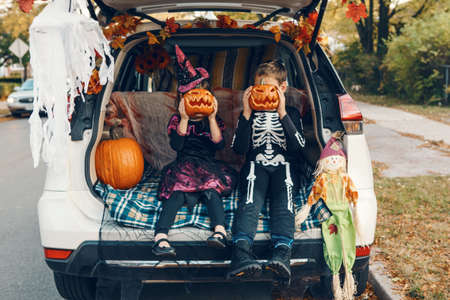 Trick or trunk. Siblings brother and sister celebrating Halloween in trunk of car. Children kids boy and girl celebrating October holiday outdoor. Social distance and safe alternative celebration. Imagens