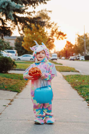 Trick or treat. Happy baby toddler with red pumpkin and basket going to trick or treat on Halloween holiday. Cute child kid in party costume going to neighbour houses for candies and treats.