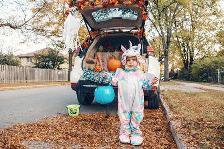 Trick or trunk. Sad upset baby in unicorn costume celebrating Halloween in trunk of car. Cute toddler preparing for October holiday outdoor. Social distance and safe alternative celebration.