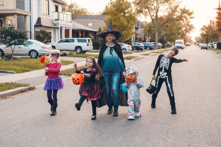 Trick or treat. Mother with children going to trick or treat on Halloween holiday. Mom with kids in party costumes with baskets going to neighbourhood houses for candies, treats.