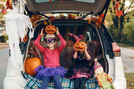 Trick or trunk. Children siblings sisters celebrating Halloween in trunk of car. Friends kids girls preparing for October holiday outdoor. Social distance and safe alternative celebration.