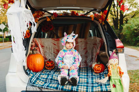 Trick or trunk. Sad upset baby in unicorn costume celebrating Halloween in trunk of car. Cute toddler celebrating October holiday outdoor. Social distance and safe alternative celebration.