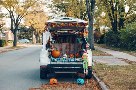 Trick o trunk. White car trunk decorated for Halloween. Autumn fall decor with red pumpkins and yellow leaves for traditional October holiday outdoor. Social distance and alternative safe celebration Imagens