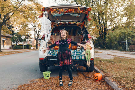 Trick or trunk. Kid child celebrating traditional October holiday Halloween in trunk of car. Cute happy girl throwing leaves in air outdoor. Social distance and safe alternative celebration.