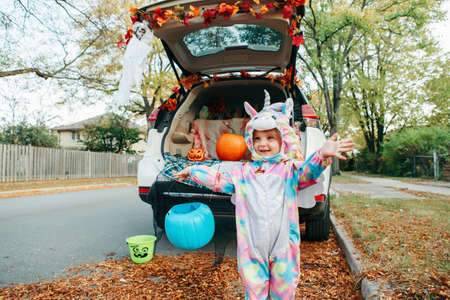 Trick or trunk. Happy baby in unicorn costume celebrating Halloween in trunk of car. Cute smiling toddler preparing for October holiday outdoor. Social distance and safe alternative celebration.
