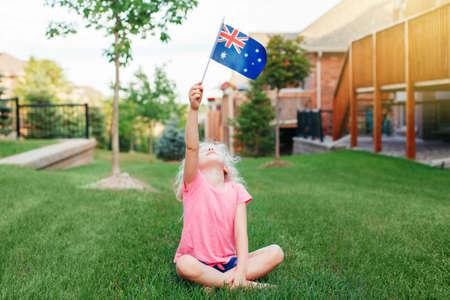 Adorable cute happy Caucasian girl holding Australian flag. Smiling child sitting on grass in park holding Australia flag. Kid citizen celebrating Australia Day holiday in January outdoor. Banco de Imagens