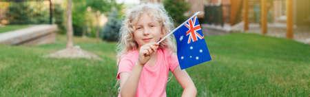 Happy Caucasian girl holding Australian flag. Smiling child sitting on grass holding Australia flag. Kid citizen celebrating Australia Day holiday in January outdoor. Web banner header. Banco de Imagens