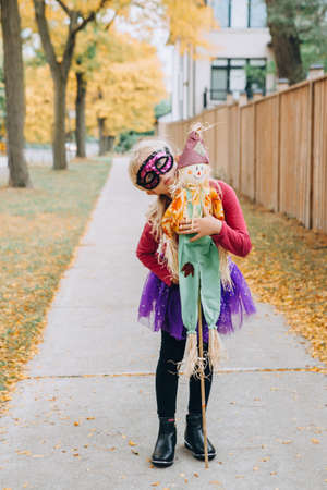 Trick or treat. Happy child going to trick or treat on Halloween outdoor. Kid girl in party costume with scarecrow going to neighbour houses for candies and treats. Themed party event.