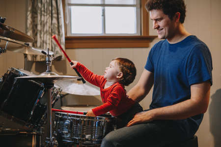 Father teaching baby boy to play drums. Parent with toddler child having fun and spending time together. Dad and kid playing music. Family hobby activity and leisure time. Fathers Day.