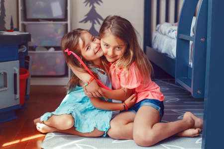 Two cute Caucasian girls siblings hugging together. Happy smiling friends family relationship concept. Adorable children playing together. Authentic candid lifestyle domestic life moment. Banco de Imagens