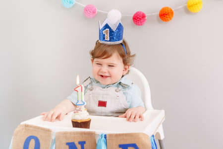 Happy smiling cute Caucasian baby boy in blue crown celebrating his first birthday at home. Child kid toddler sitting in high chair eating tasty cupcake dessert with lit candle. Happy birthday concept