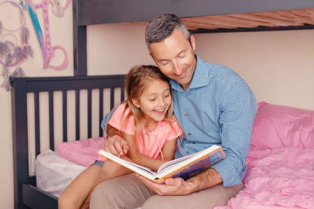 Dad reading book to daughter girl. Happy family of two sitting on bed in bedroom. Smiling father and child at home spending time together. Fathers Day. Authentic lifestyle childhood.