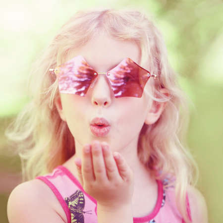 Young girl posing in fancy pink pentagonal shaped sunglasses outdoor. Cute adorable stylish Caucasian child with long blonde hair sending air kiss. Cool hipster kid having fun.