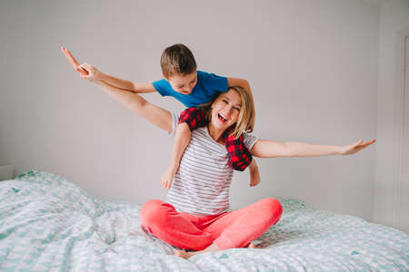 Smiling Caucasian mother and boy son playing in bedroom at home. Child sitting on mom shoulders and laughing. Family having fun together. Happy childhood candid authentic lifestyle. Banco de Imagens