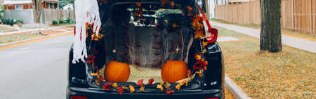 Trick or trunk. Black car trunk decorated for Halloween. Autumn fall decor with red pumpkins and yellow leaves for traditional October holiday outdoor. Web banner header.