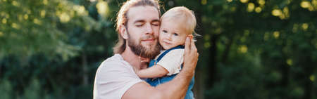 Proud father hugging embracing toddler baby boy. Young parent holding child son on arms. Authentic lifestyle tender moment. Single dad family life. Happy fatherhood. Web banner header. Banco de Imagens