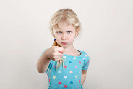 Child girl showing fig sign. Kid expressing strong negative emotion. Cute adorable blonde Caucasian preschool girl posing in studio on light background.