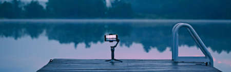 New technology. Smartphone standing on gimbal tripod outdoor for stabilisation video. Modern tool camera equipment for bloggers and vloggers. Web banner header.