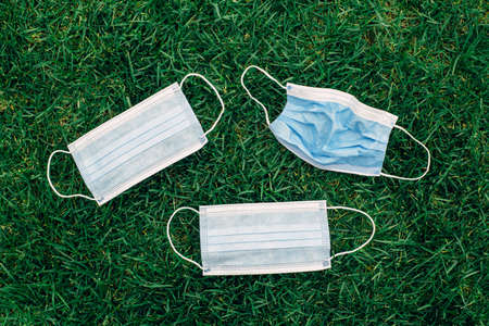 Group of used and fresh sanitary masks lying on grass. Disposable recyclable face mask flat lay. Coronavirus, medicine and seasonal allergy concept. View from top above overhead.