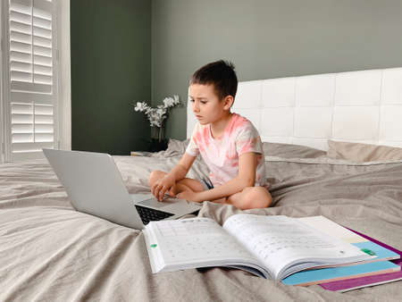Caucasian boy child sitting in bed and learning online on laptop Internet. Virtual class lesson on video. Self isolation at home. Distant remote video education. New normal school study for kids.