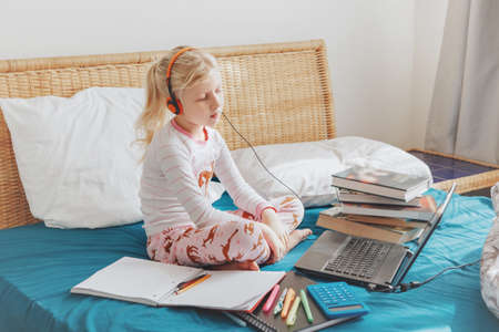 Caucasian girl child sitting in bed and learning online on laptop Internet. Virtual class lesson school on video chat during self isolation quarantine at home. Distant remote video education class.