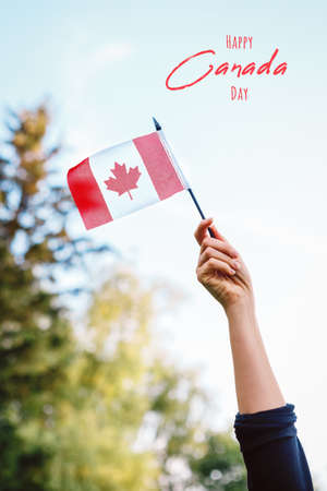 Happy Canada Day card with text. Closeup of woman human hand arm waving Canadian flag against blue sky. Proud citizen man celebrating national Canada Day on 1st of July outdoor.