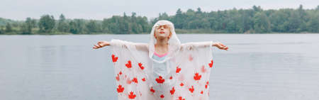 Girl child in rain poncho with red maple leaves standing by lake. Kid raising arms up high under rain outdoor. Connection with nature. Freedom and happy childhood lifestyle. Web banner header.