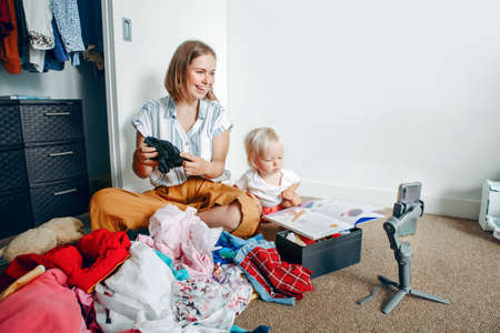 Young mother blogger doing video live stream for social media while sorting clothes at home. Video call chat with friends and family on smartphone. Woman using gimbal tripod for video and phone calls.