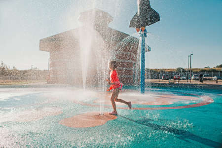 Cute adorable Caucasian funny girl playing on splash pad playground on summer day. Happy child having fun in water. Seasonal water sport recreational activity for kids outdoor.