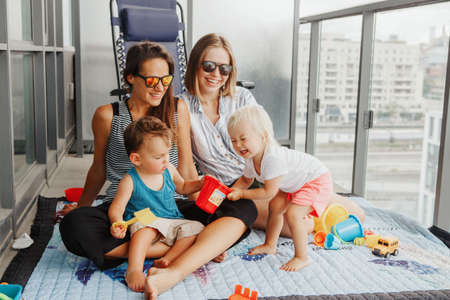 Young mothers spending time together with children babies on balcony at home. LGBTQ female parents playing with kids. Staycation during coronavirus covid-19 pandemic in the world.