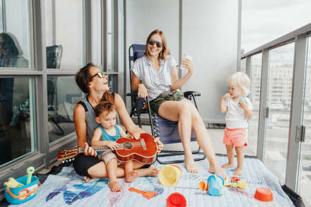 Young mothers spending time together with children babies on balcony at home. Staycation during coronavirus covid-19 pandemic in the world. Preventive measures against virus spread.