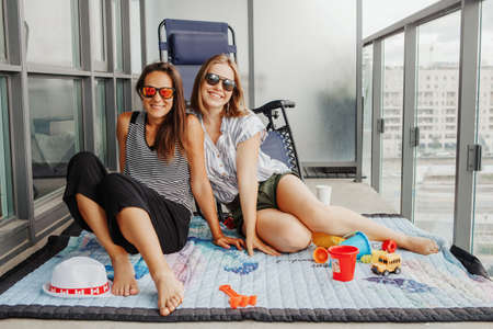Young lgbtq women family spending time together on balcony at home. Happy women smiling females in sunglasses. Staycation during coronavirus covid-19 pandemic in the world.