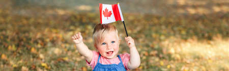 Adorable cute little Caucasian baby toddler girl waving Canadian flag in park outdoor. Kid child citizen sitting on ground in park and celebrating Canada Day on 1st of July. Web banner header.