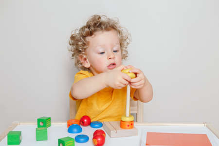 Cute baby toddler playing with learning toy pyramid stacking blocks at home or kindergarten. Early age education. Kids hand brain fun development activity for preschoolers. Stock fotó