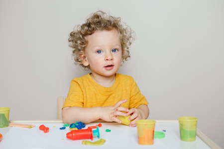 Cute Caucasian blond curly baby boy child playing with sensor kinetic toy . Hand brain development activity for young toddler kids. Early age preschool education.