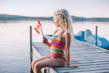 Happy Caucasian girl sitting on dock pier by lake and waving Canadian flag. Smiling child holding Canada flag sitting by water. Kid citizen celebrating Canada Day holiday on first day of July outdoor.