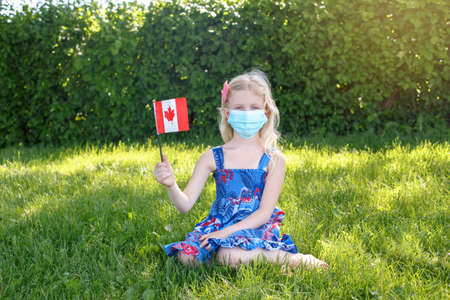 Caucasian girl in face protective mask holding waving Canadian flag outdoor. Child kid in sanitary mask on grass in park celebrating Canada Day holiday during epidemic.