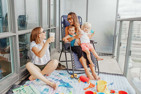 Young mothers spending time together with children babies on balcony at home.