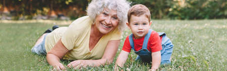 Grandmother with grandson boy at home backyard. Bonding of relatives and generation communication. Old woman with baby having fun spending time together outdoor. Web banner header.