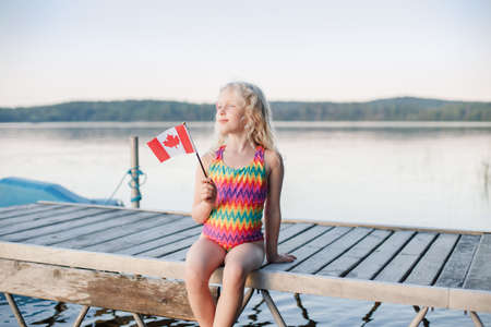 Happy Caucasian girl sitting on pier by lake and waving Canadian flag. Smiling child holding Canada flag by water. Kid celebrating Canada Day holiday on first day of July outdoor
