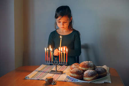 Girl lighting candles on menorah for traditional winter Jewish Hanukkah holiday at home. Child celebrating Chanukah festival of lights. Dreidel and Sufganiyot donuts in plate on table. Israel holiday.