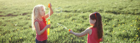 Catch a bubble. Girls friends blowing soap bubbles in park on summer day. Kids having fun outdoor. Authentic happy childhood magic moment. Lifestyle seasonal activity for children. Web banner header.