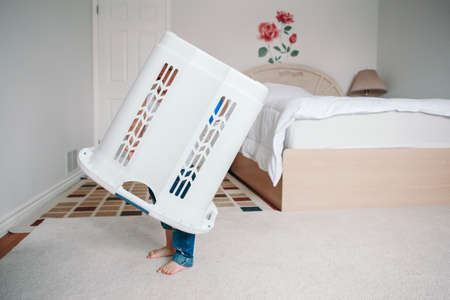 Cute funny baby toddler child with large clothes bin on head. Lonely autistic kid playing alone at home hide and seek game. Funny memorable childhood moment. Home authentic lifestyle.