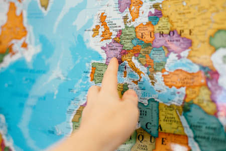 Toronto, Ontario, Canada - February 26, 2021: Human hand finger pointing out to Europe country on map. Travel dream destination. France country landmark on world global colorful map.