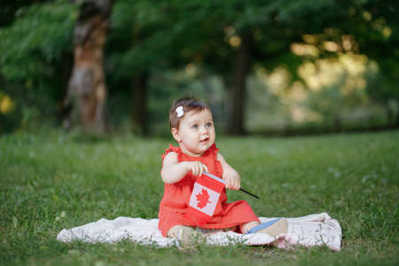 Adorable cute little Caucasian baby toddler girl in red dress waving Canadian flag in park outdoors. Kid child citizen sitting on ground in park and celebrating Canada Day on 1st of July.