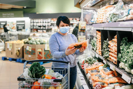 Grocery shopping. Middle age woman with short dark hair in blue protective face mask choosing buying food in supermarket and putting in shopping cart. New normal at coronavirus covid-19.