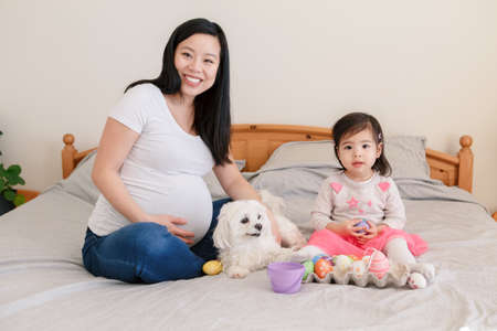 Happy Easter. Asian Chinese pregnant mother with baby girl playing with colorful Easter eggs on bed at home. Kid child and parent celebrating traditional Christian holiday.
